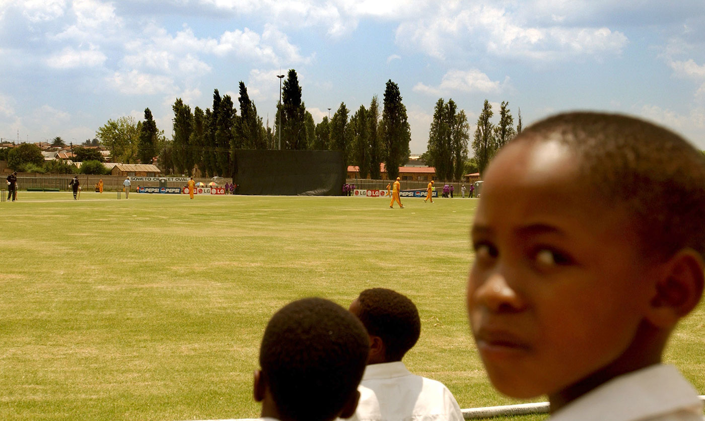 School kids watch a warm-up match between New Zealand and Gauteng at the Soweto Cricket Oval