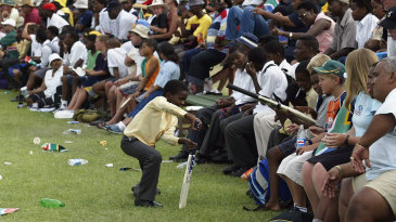 A young boy practises his batting technique at the sidelines of a World Cup game in East London