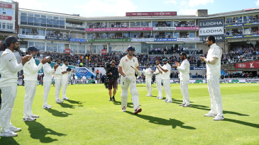 Alastair Cook walks out to bat through a guard of honour