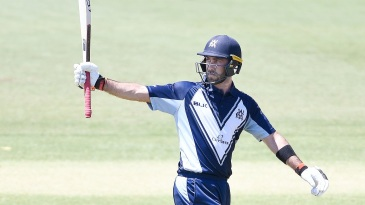 Glenn Maxwell raises his bat after getting to a fifty