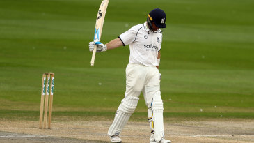 Ian Bell raises his bat after reaching fifty
