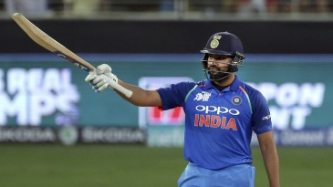 Rohit Sharma raises his bat after getting to his half-century