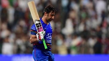 Asghar Afghan raises his bat while walking off