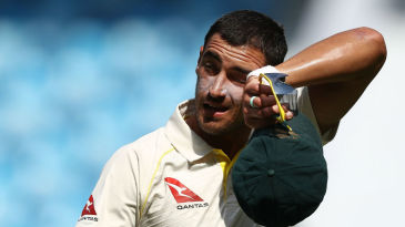Mitchell Starc wipes sweat off his forehead after his first spell
