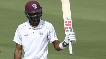 Roston Chase raises his bat after bringing up a fifty