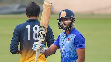 Shreyas Iyer raises his bat as he gets to fifty