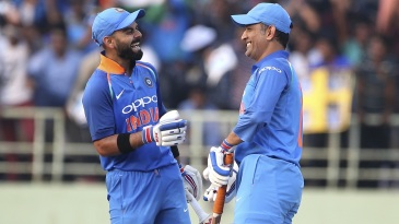 Virat Kohli and MS Dhoni meet mid-pitch while the ball is retrieved from the stands