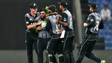 Ajaz Patel is mobbed by teammates after snaring his maiden international wicket