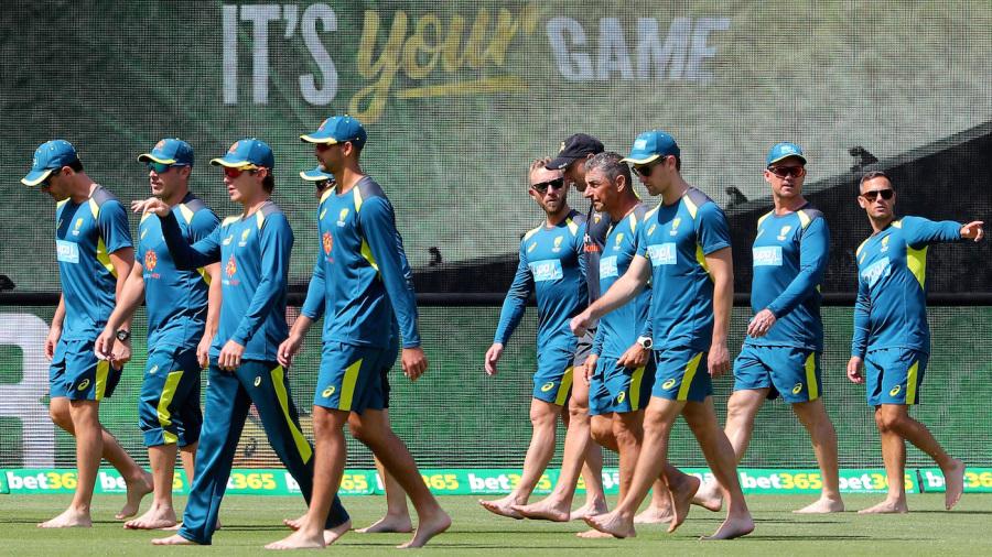 The Australian players walk barefoot around the Perth Stadium