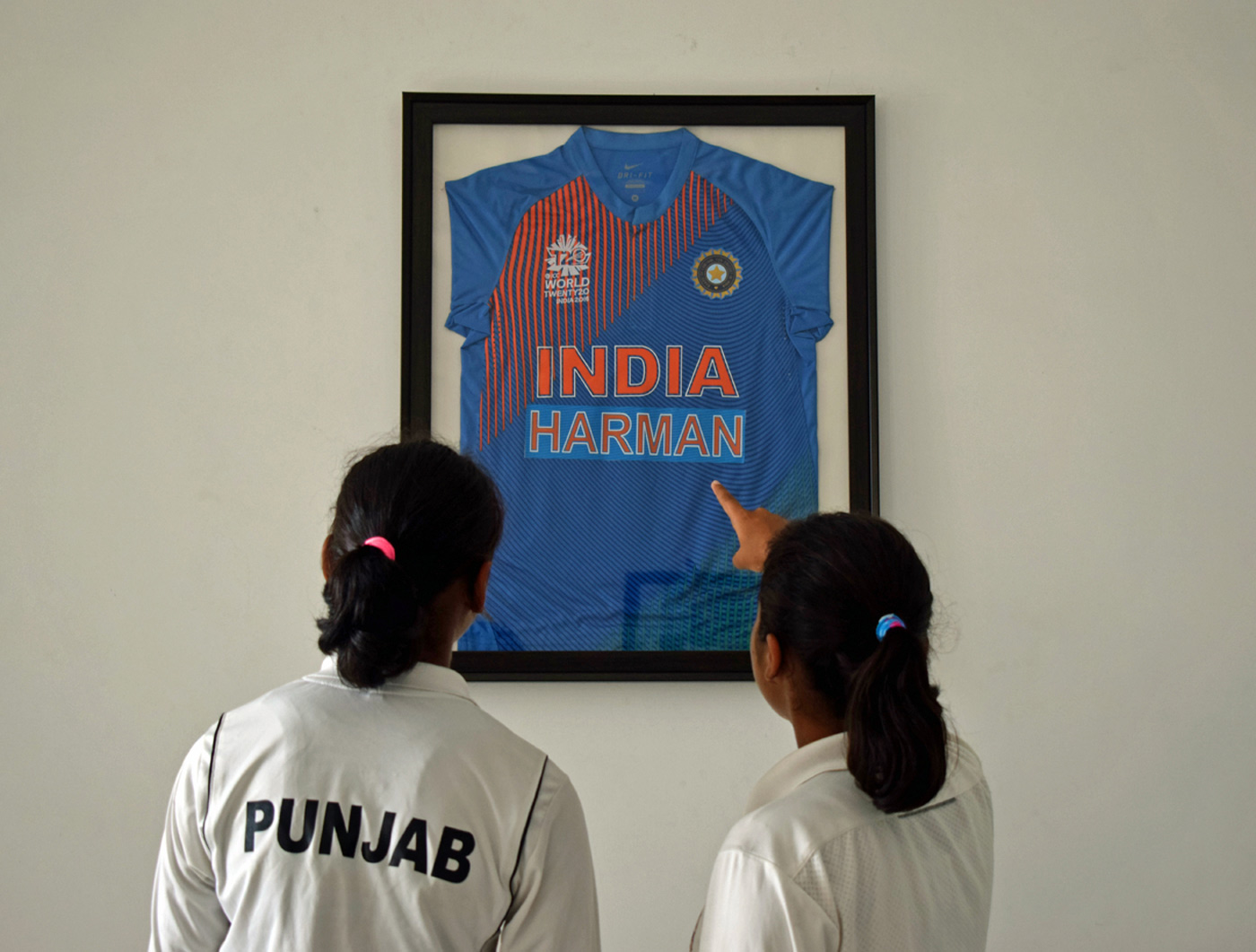 Someday that'll be us: cricketers Avneet Kaur and Ramanpreet Kaur look at a framed jersey of Harmanpreet's in the office of Kamaldheesh Sodhi, the founder of Gian Jyoti School