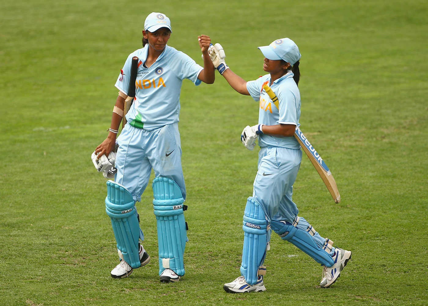 Harmanpreet and Amita Sharma (right) walk off the ground after sealing the 2009 World Cup game against Australia