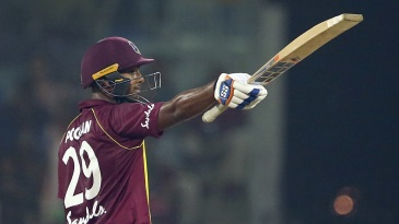 Nicholas Pooran raises his bat after reaching a half-century