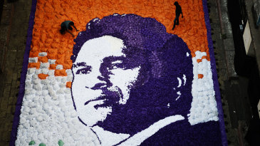 Artists complete a portrait of Sachin Tendulkar made with pieces of paper for his 45th birthday