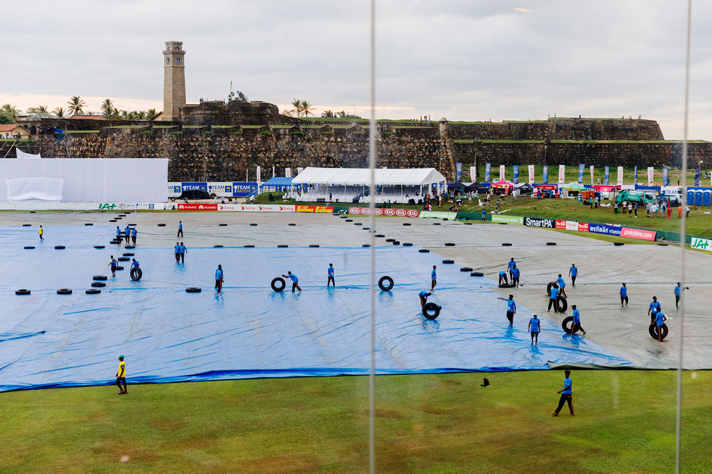 Ground staff pull on the covers to keep the ground dry during a spell of rain