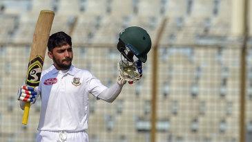 Mominul Haque raises his bat after bringing up his hundred
