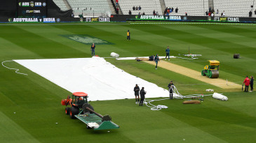 Ground staff at work on a rainy day at the MCG