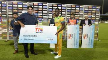 Arvinder Singh, the T10 League CEO, hands over the Player of the Match cheque to Andre Fletcher