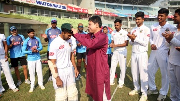 Chief selector Minhajul Abedin presents debutant Shadman Islam with a cap