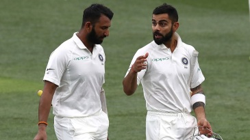 An animated Virat Kohli speaks to Cheteshwar Pujara as they walk off for tea