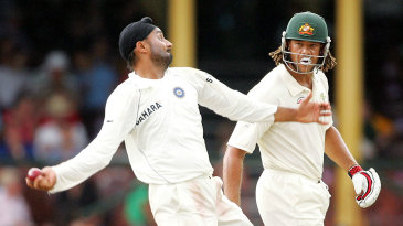 Andrew Symonds watches Harbhajan Singh bowl