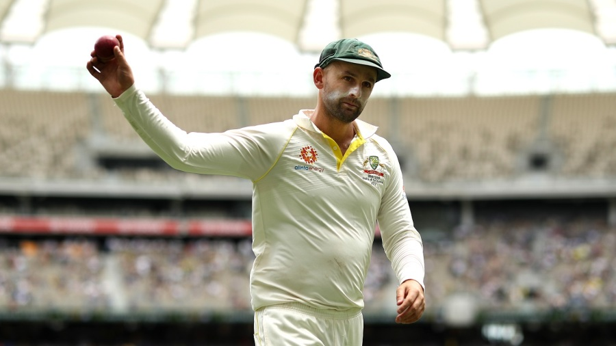 Nathan Lyon raises the ball aloft after claiming his seventh five-for against India