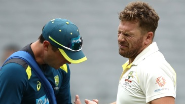 Aaron Finch in pain as the physio takes a look at his injury