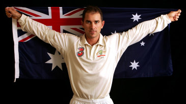 Justin Langer poses with the Australian flag