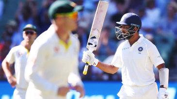 Cheteshwar Pujara raises the bat after getting his fifty