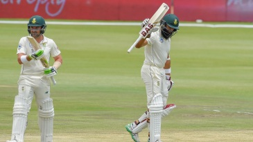 Hashim Amla raises his bat after reaching fifty while Dean Elgar applauds