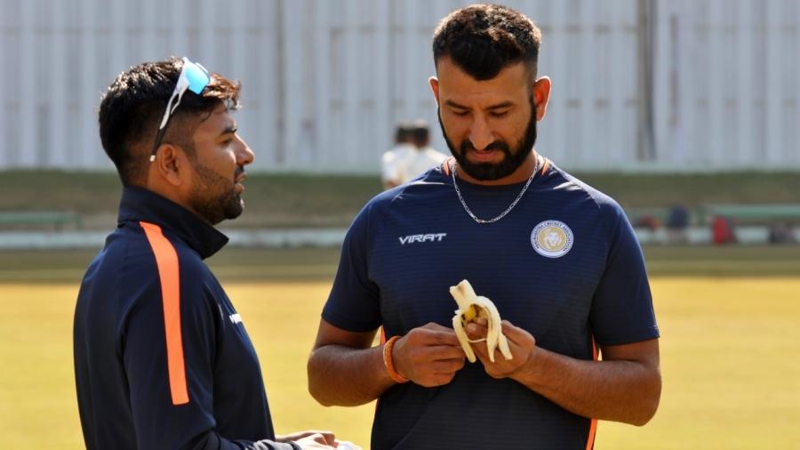 Cheteshwar Pujara having a banana during a practice session