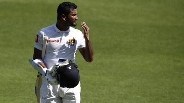 Dimuth Karunaratne walks back after slashing a cut to the keeper