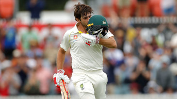 Joe Burns kisses the badge on reaching his century