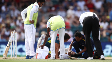 Sri Lanka's physio checks on Dimuth Karunaratne after he is hit on the head by a Pat Cummins bouncer