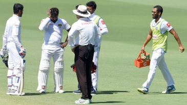 Kusal Perera receives medical attention after being hit on the helmet