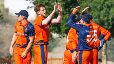 Fred Klaassen gets a round of high fives after his first wicket of the day