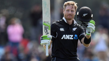 Martin Guptill raises his bat after reaching his century
