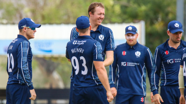 Adrian Neill celebrates with his teammates after his first wicket of the day