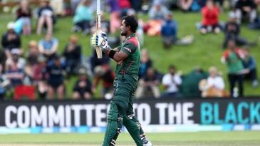 Sabbir Rahman gestures at his bat while celebrating his first international century