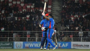 Hazratullah Zazai raises his bat after reaching his hundred