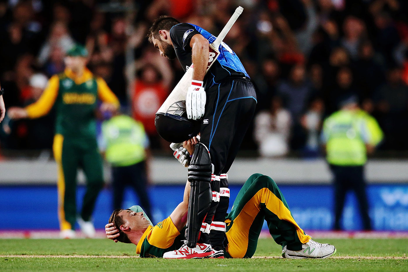 Gracious in victory: Grant Elliott helps Dale Steyn up after New Zealand won a thrilling game to qualify for their first World Cup win