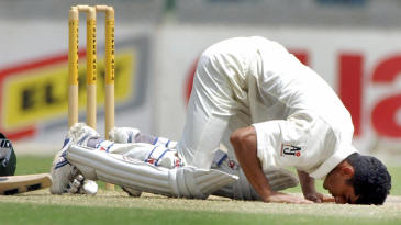Yasir Hameed touches his forehead on the pitch after his double century