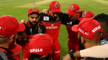 Virat Kohli leads a team huddle