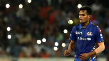 Rahul Chahar walks back to his mark
