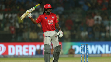 Chris Gayle raises his bat after reaching 50