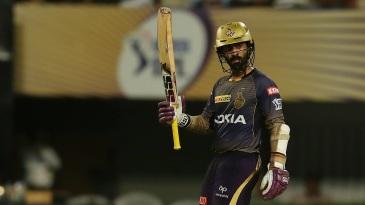 Dinesh Karthik raises his bat after reaching 50