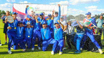 Namibia captain Gerhard Erasmus holds the WCL Division Two trophy aloft during champagne celebrations