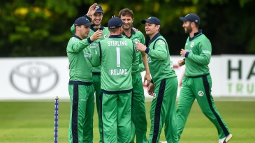 The Ireland players gather together to celebrate a wicket