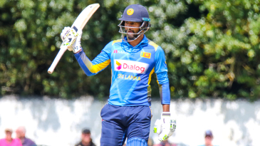 Dimuth Karunaratne raises his bat after reaching a half-century on his ODI captaincy debut