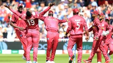 Sheldon Cottrell celebrates taking the wicket of Australia's David Warner with his teammates