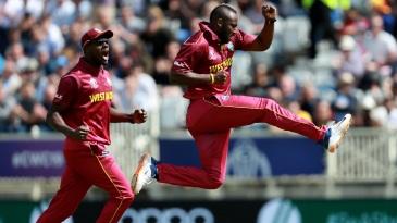Andre Russell celebrates Usman Khawaja's wicket alongside Carlos Brathwaite